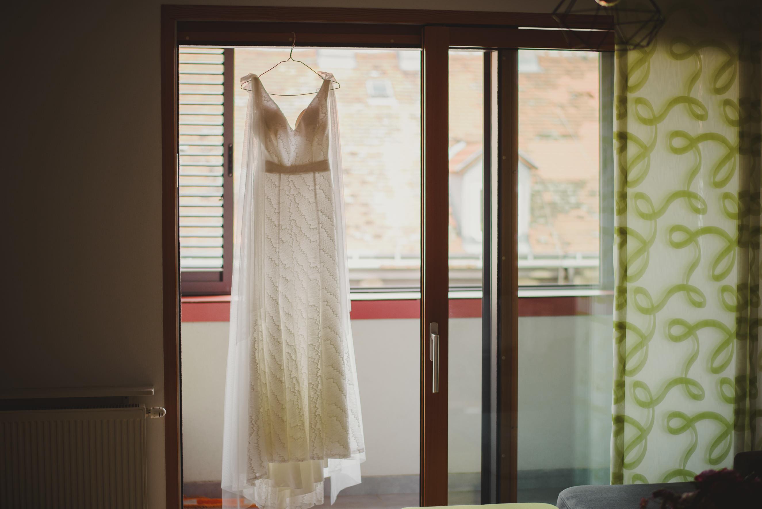wedding dress hanging in the doorway for the balcony