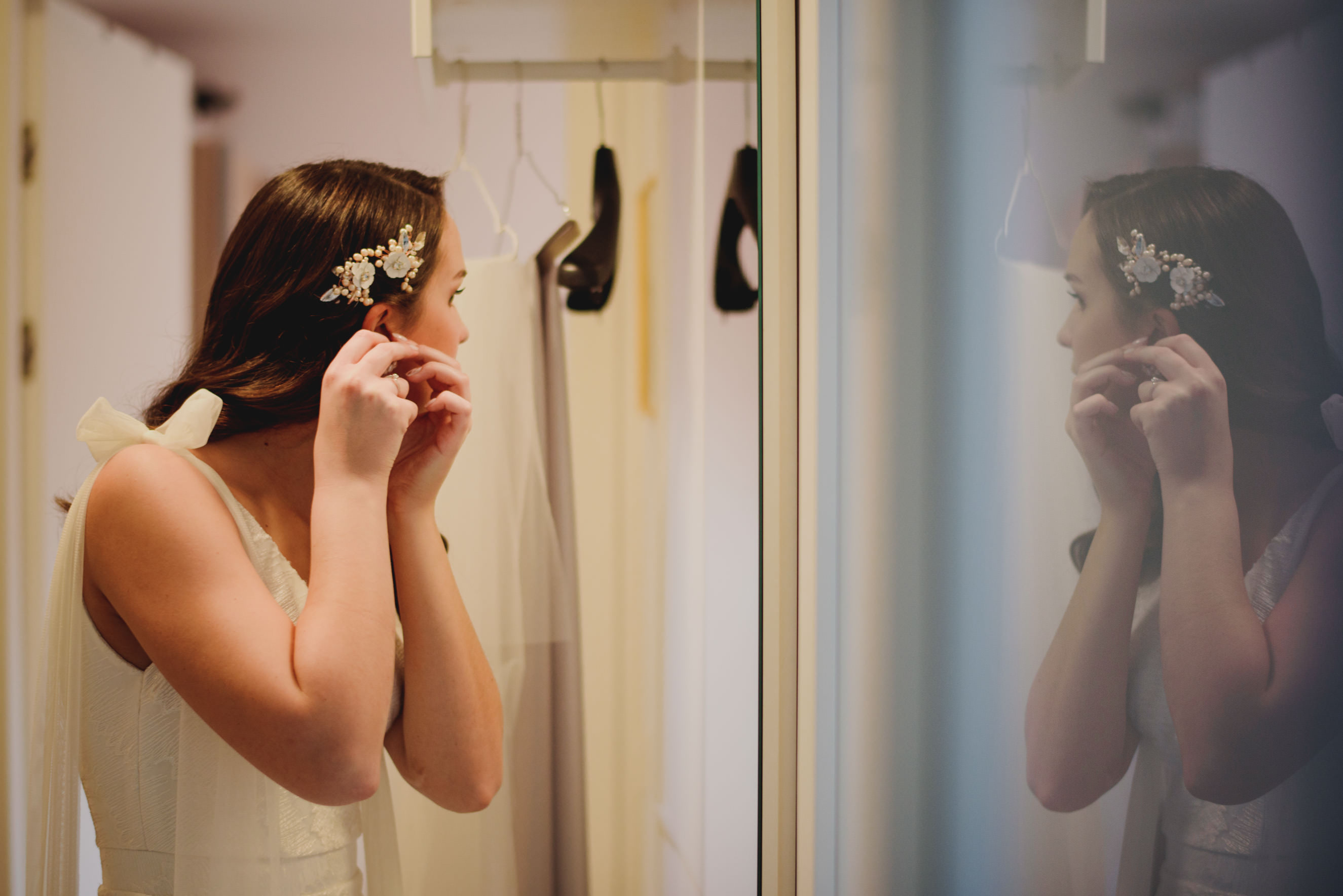 bride putting on her earrings during getting ready portion of the day