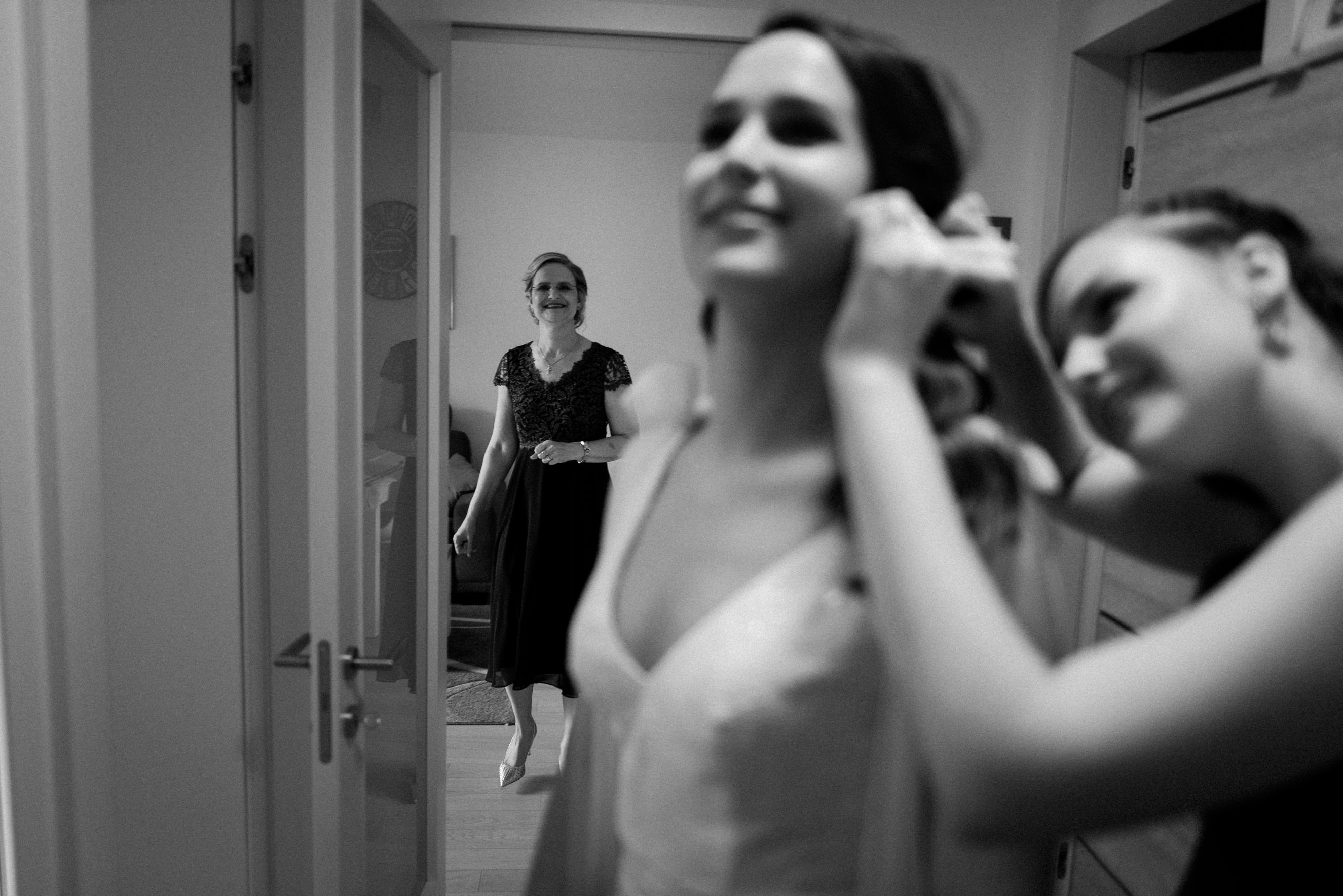 mother of the bride overlooking how brides younger sister fixes her earrings