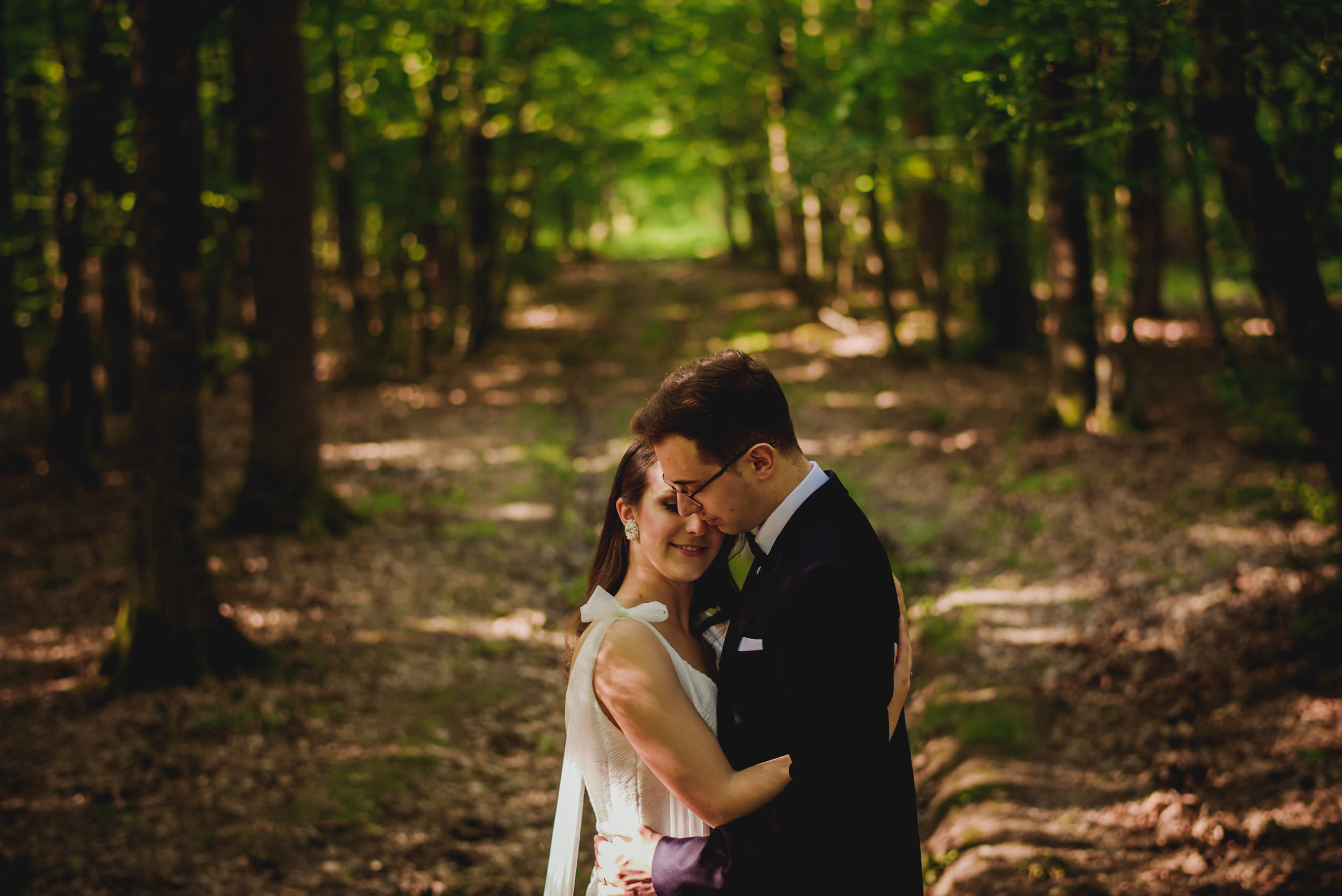 Shot of bride and groom hugging in the forrest path