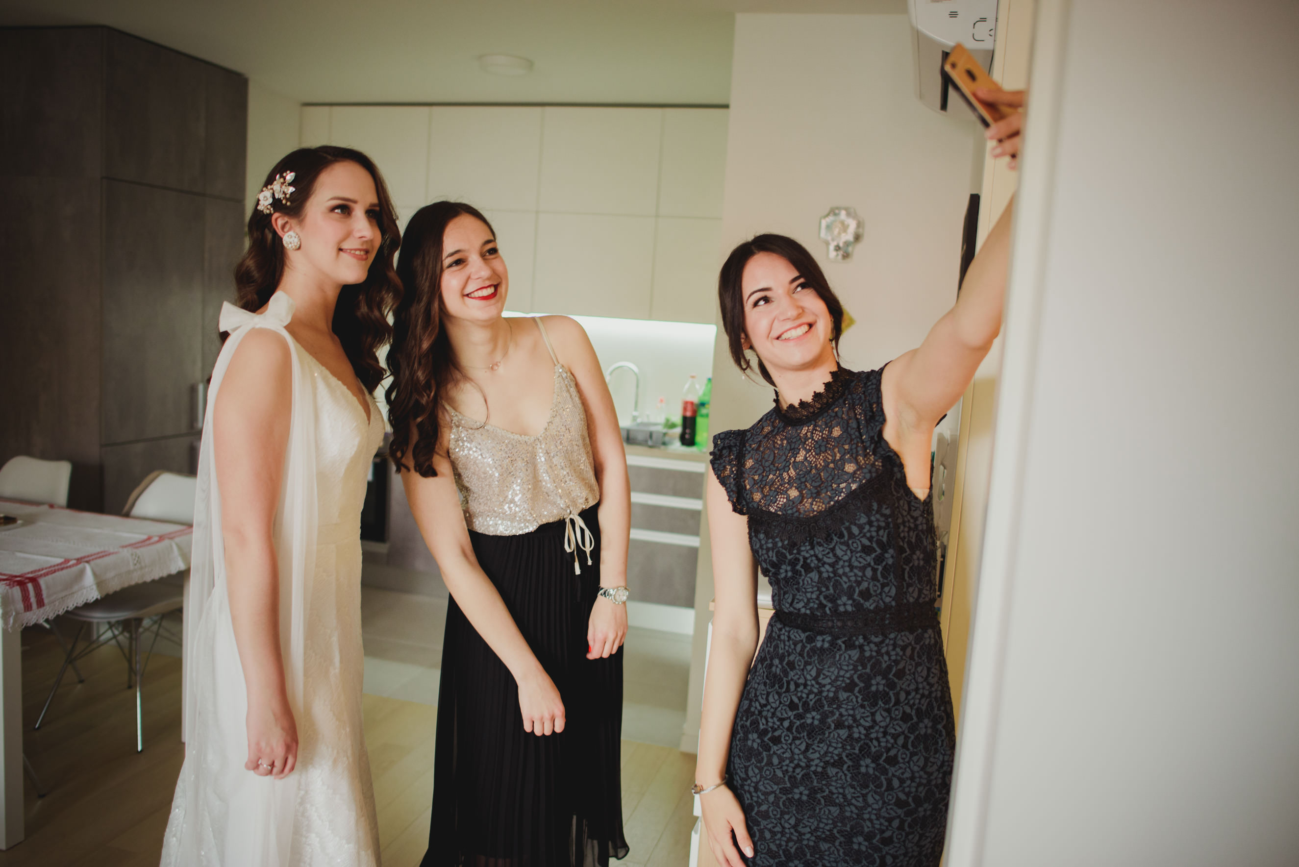 bride, maid of honour and bridesmaid taking a selfie in the living room