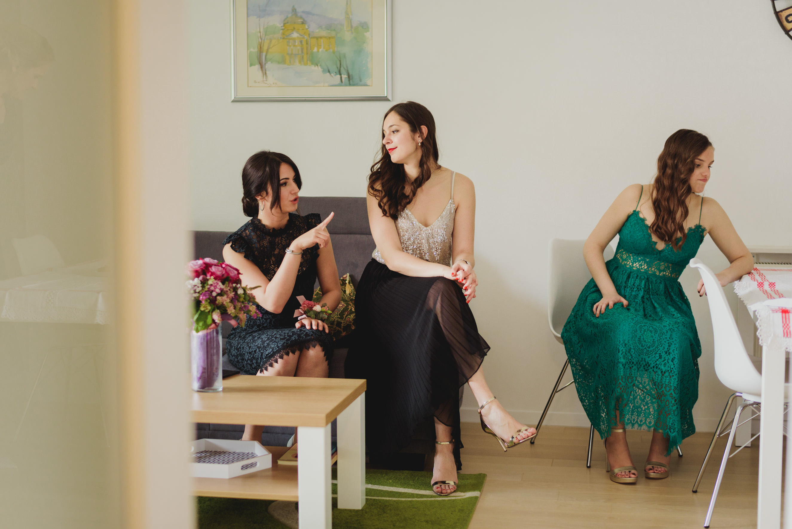 brides sister, maid of honour and bridesmaid all doing their own thing in the living room of brides and grooms apartament