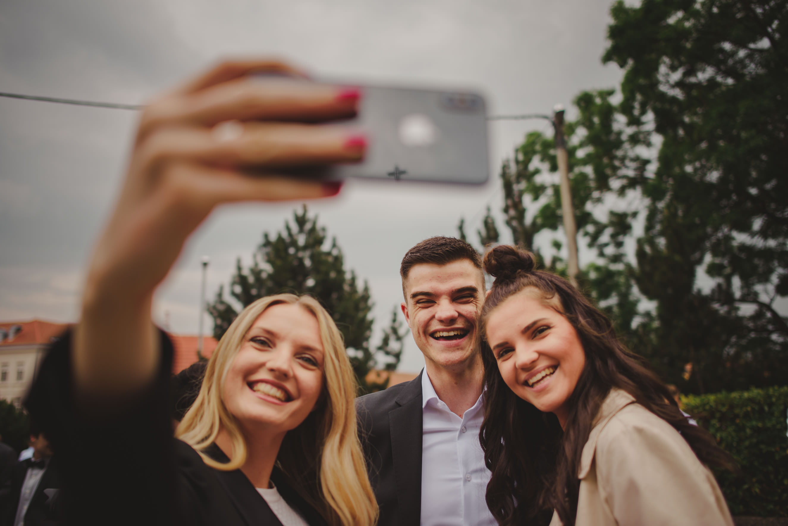 three wedding guests taking a selfie in front of the church on Sveti Duh, Zagreb