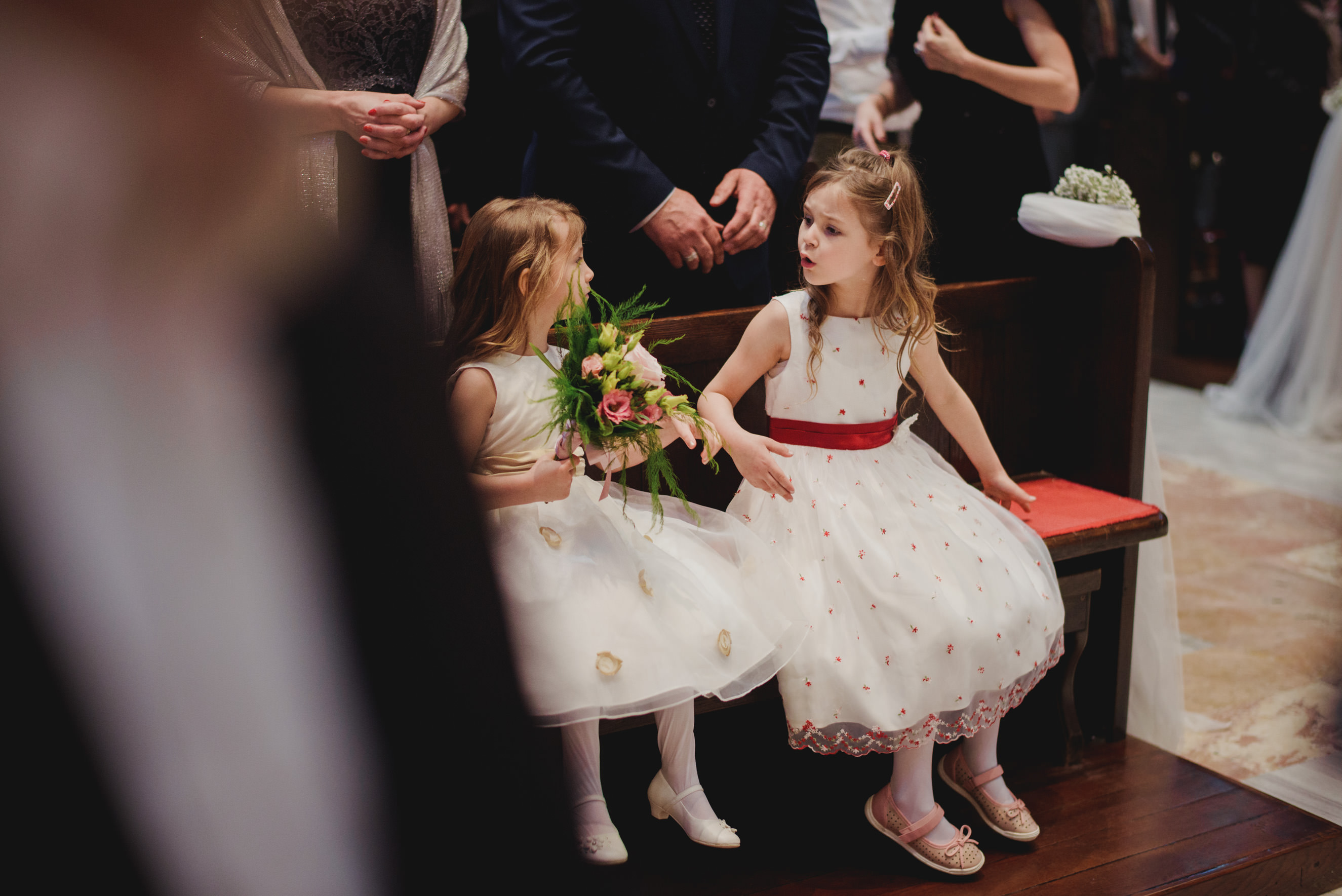 flower girls sharing a laugh in the first bench of the church