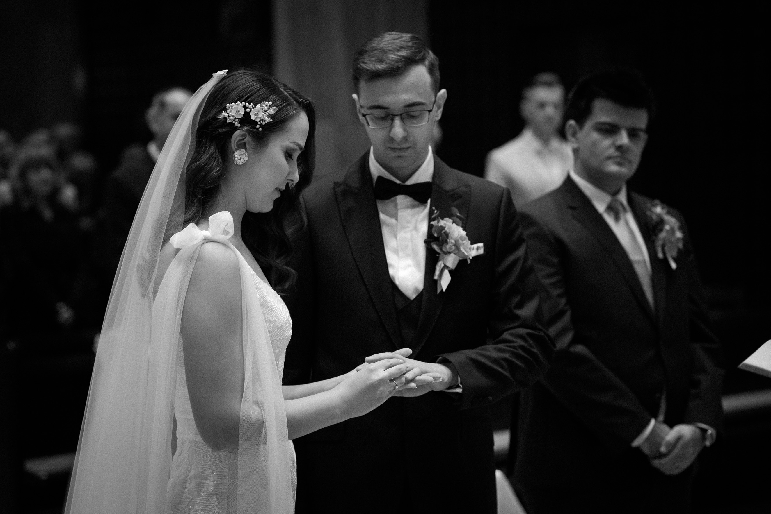 Bride putting wedding ring on groom