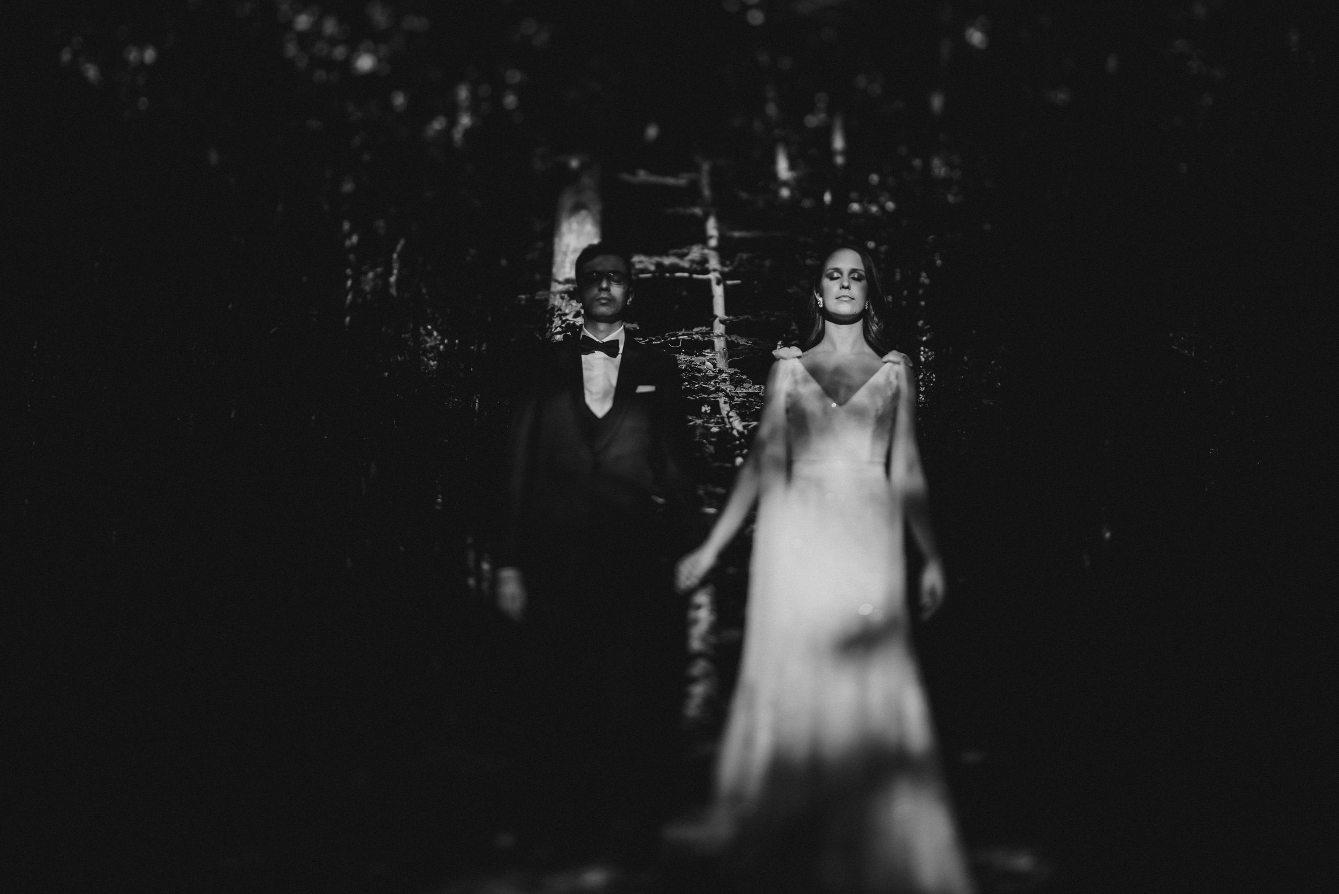 bride standing in the light in the middle of the woods holding groom hands