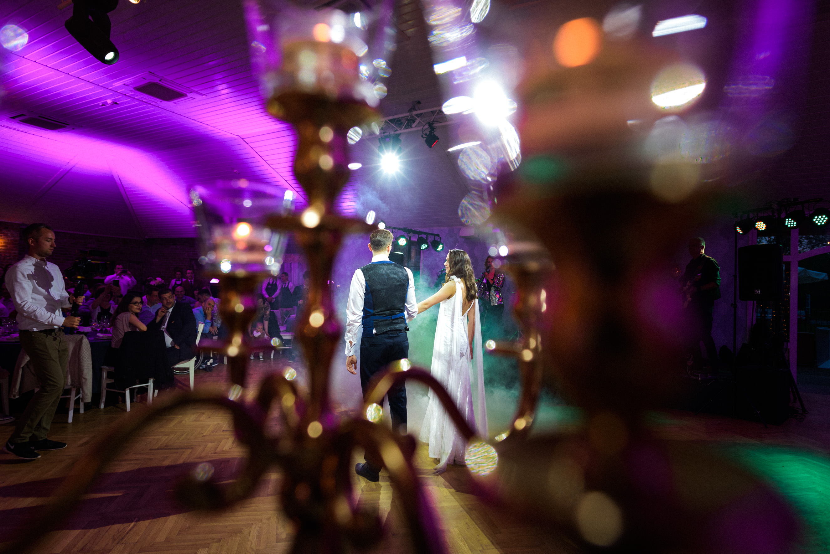 bride and groom dancing their first dance backlight by Promologistika lighting system, shot through candle holders