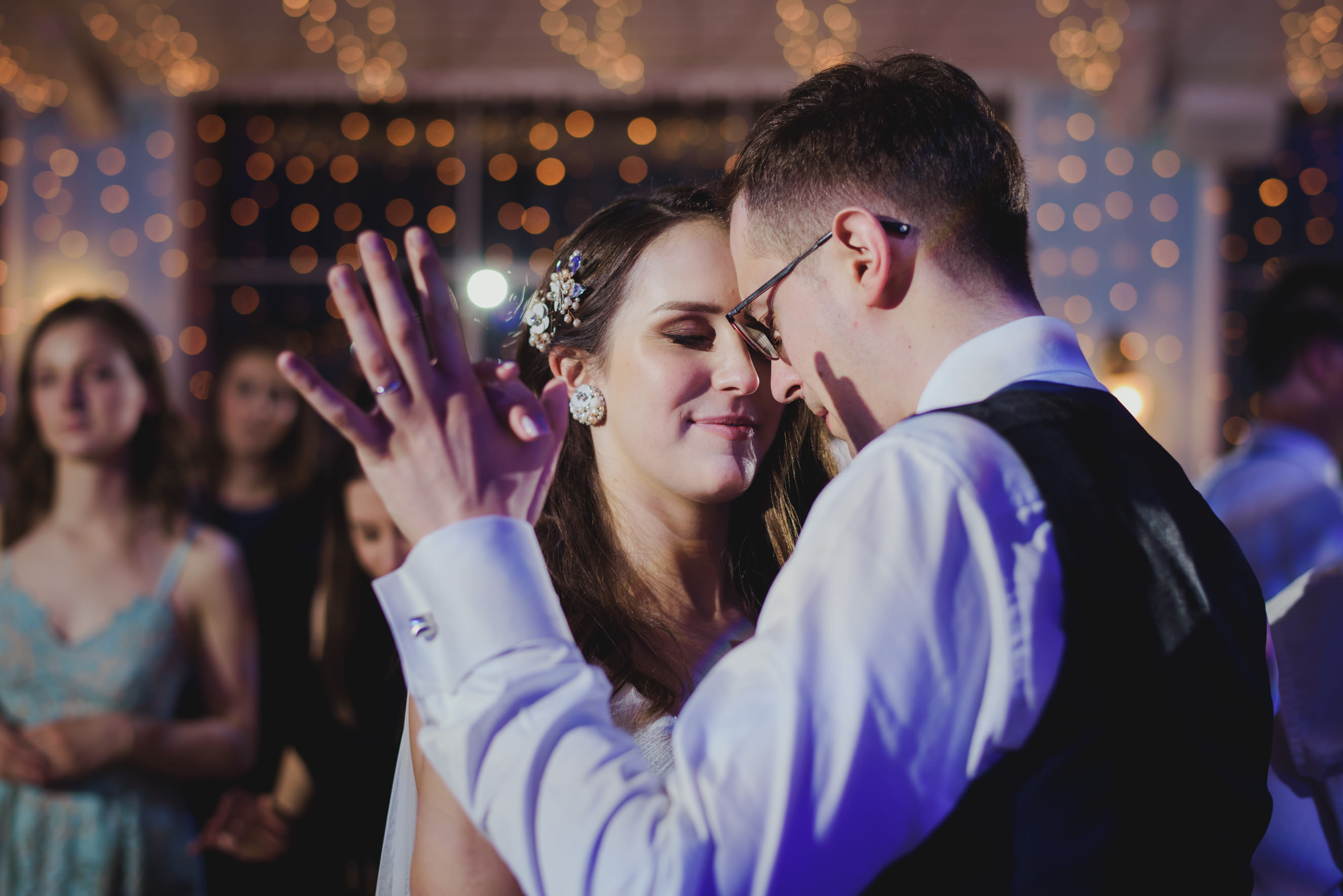 bride and groom dancing romantically to the music in the middle of the dance floor