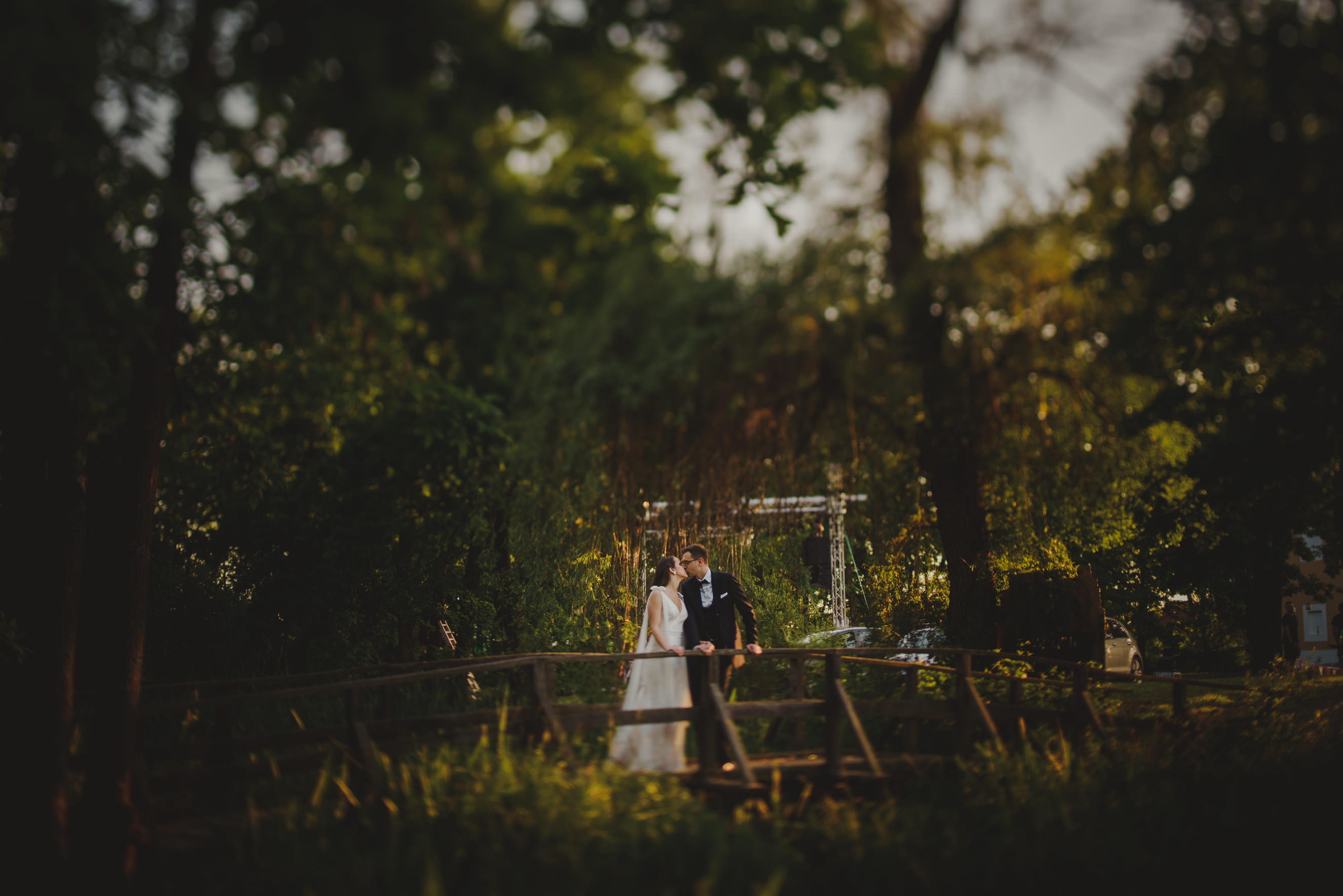 bride and groom kissing on a wooden bridge in front of Lukavec Caste near Velika Gorica