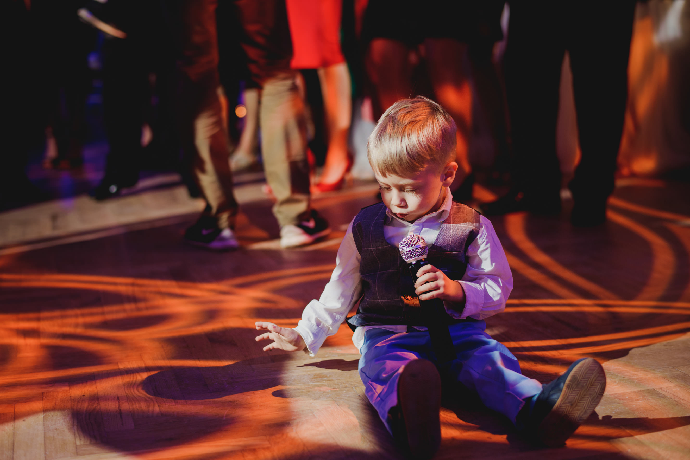 kid sitting on the floor playing with Promologistika lighting system while holding bands microphone