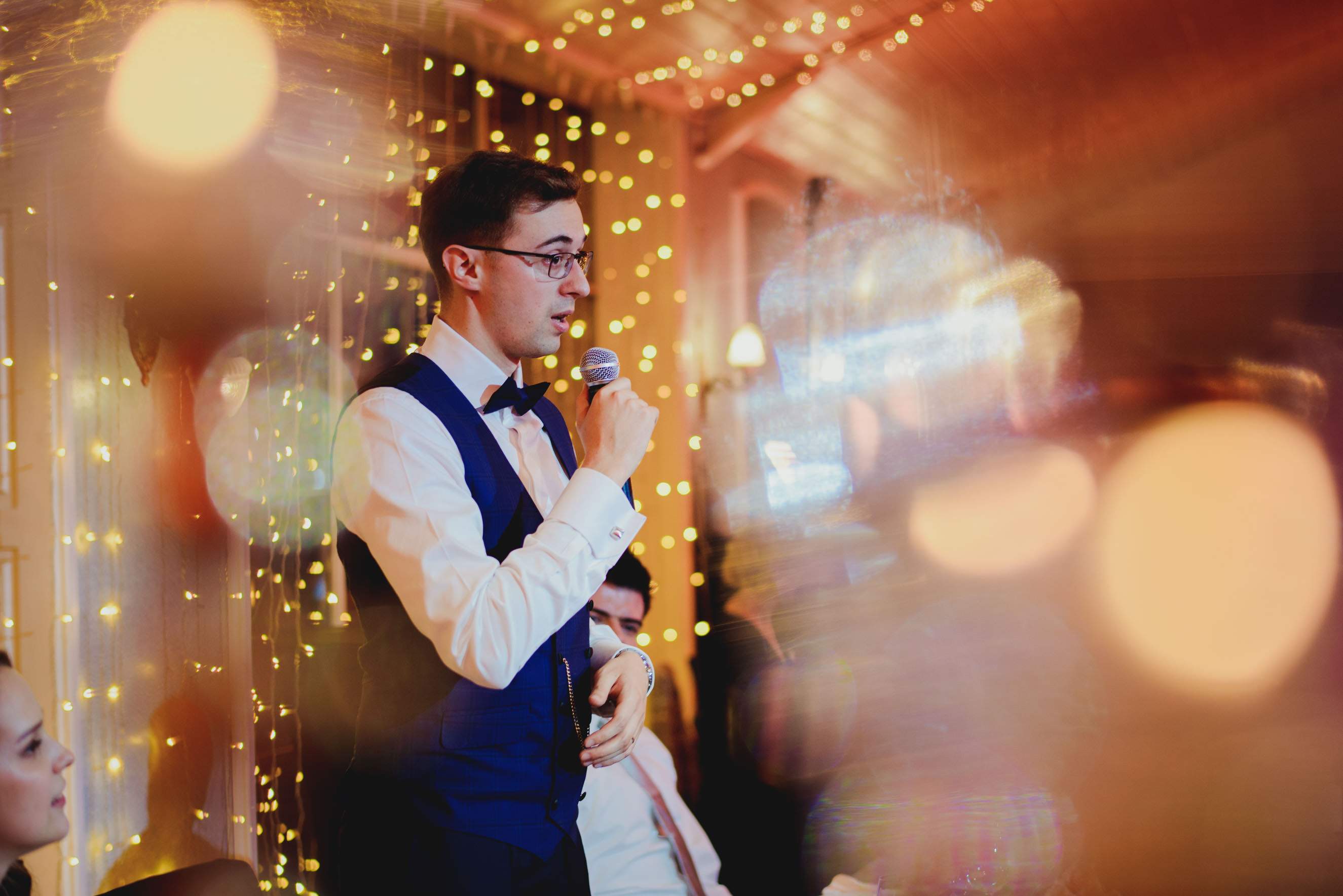 groom holding speech, shot through candle holder