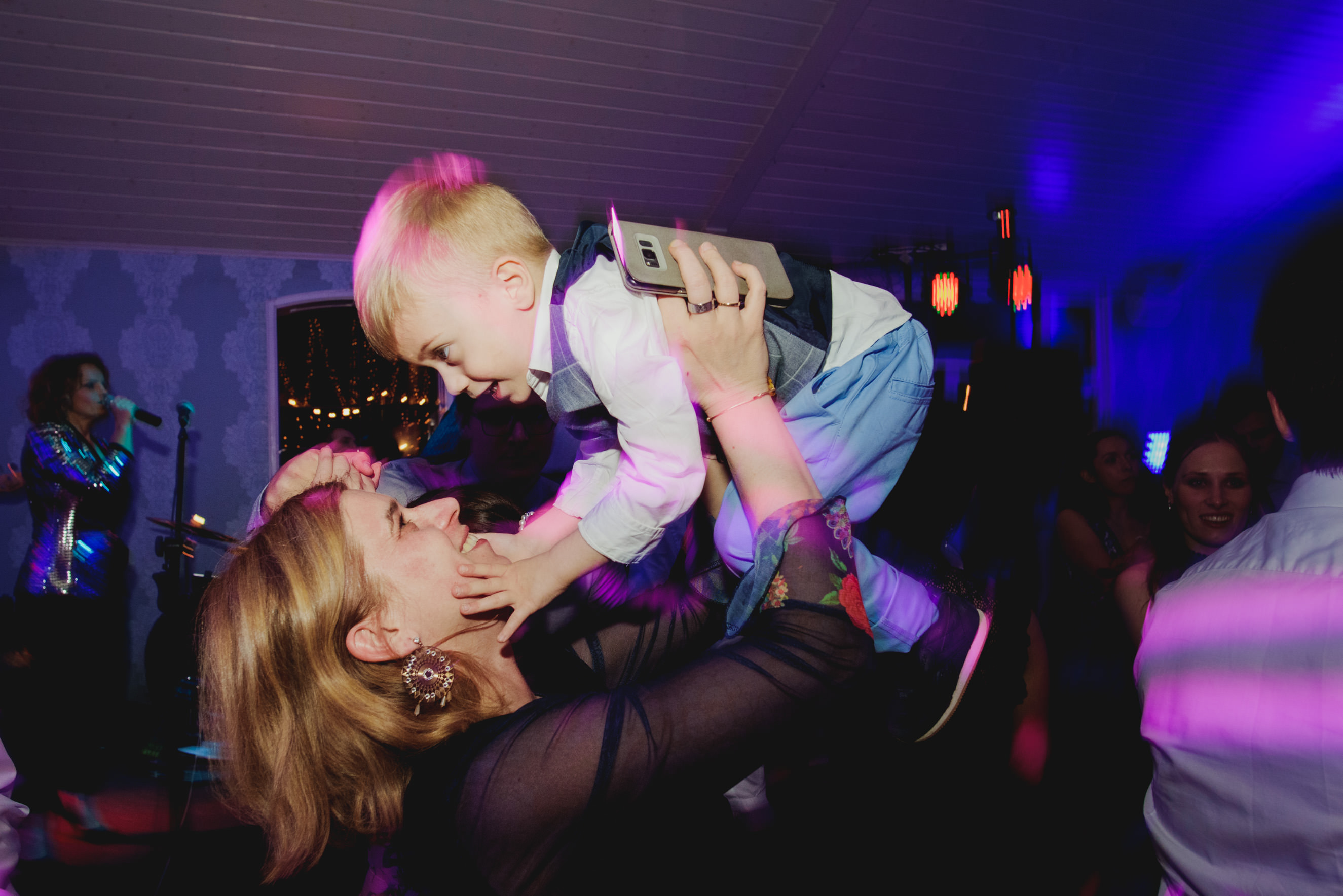 mother holding her kid above her head on the dance floor