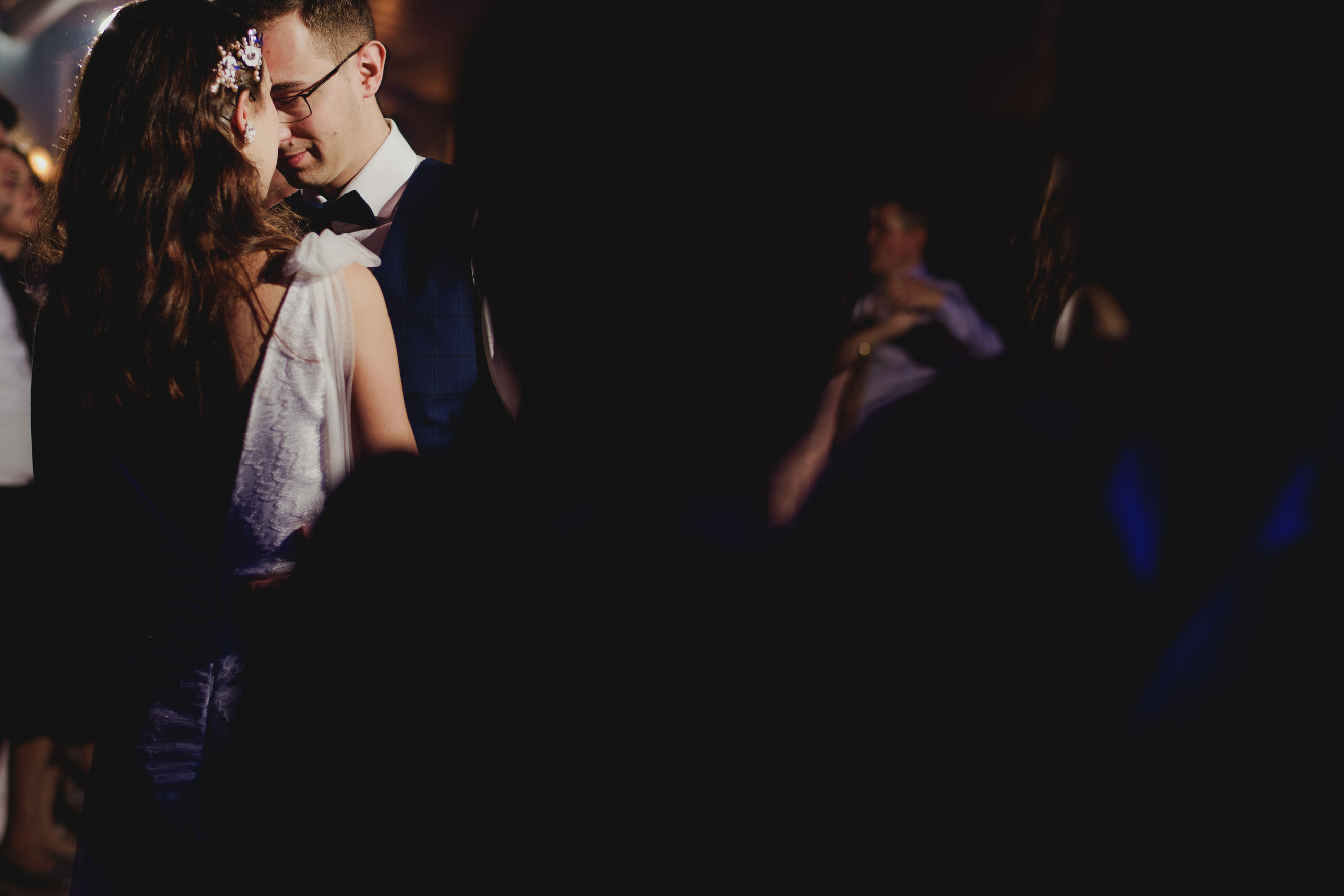bride and groom having a private moment on filled dance floor