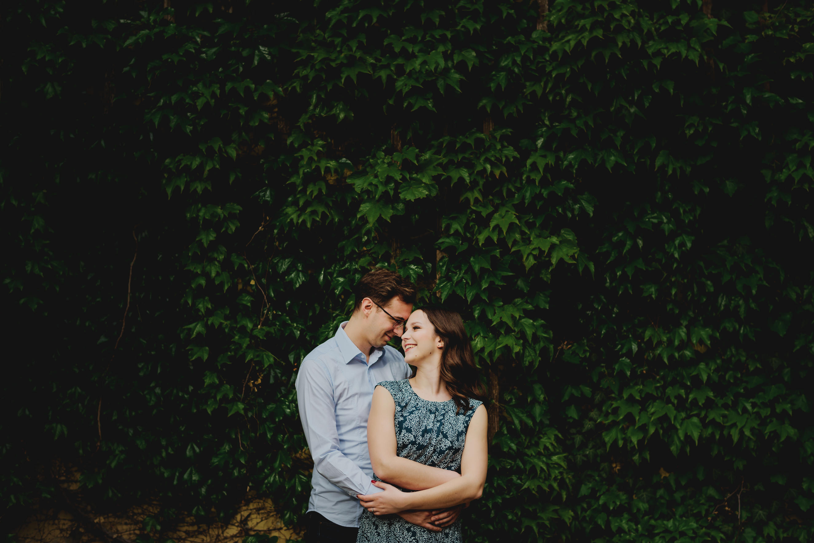 couple hugging in front of the wall filled with ivy