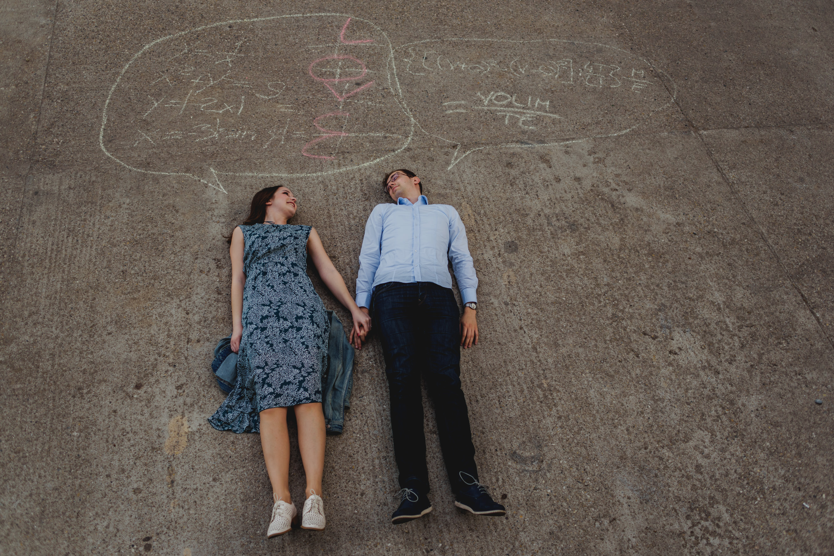 couple lying on the floor with mathematical formulas written above them. Solutions spelling LOVE and I LOVE YOU