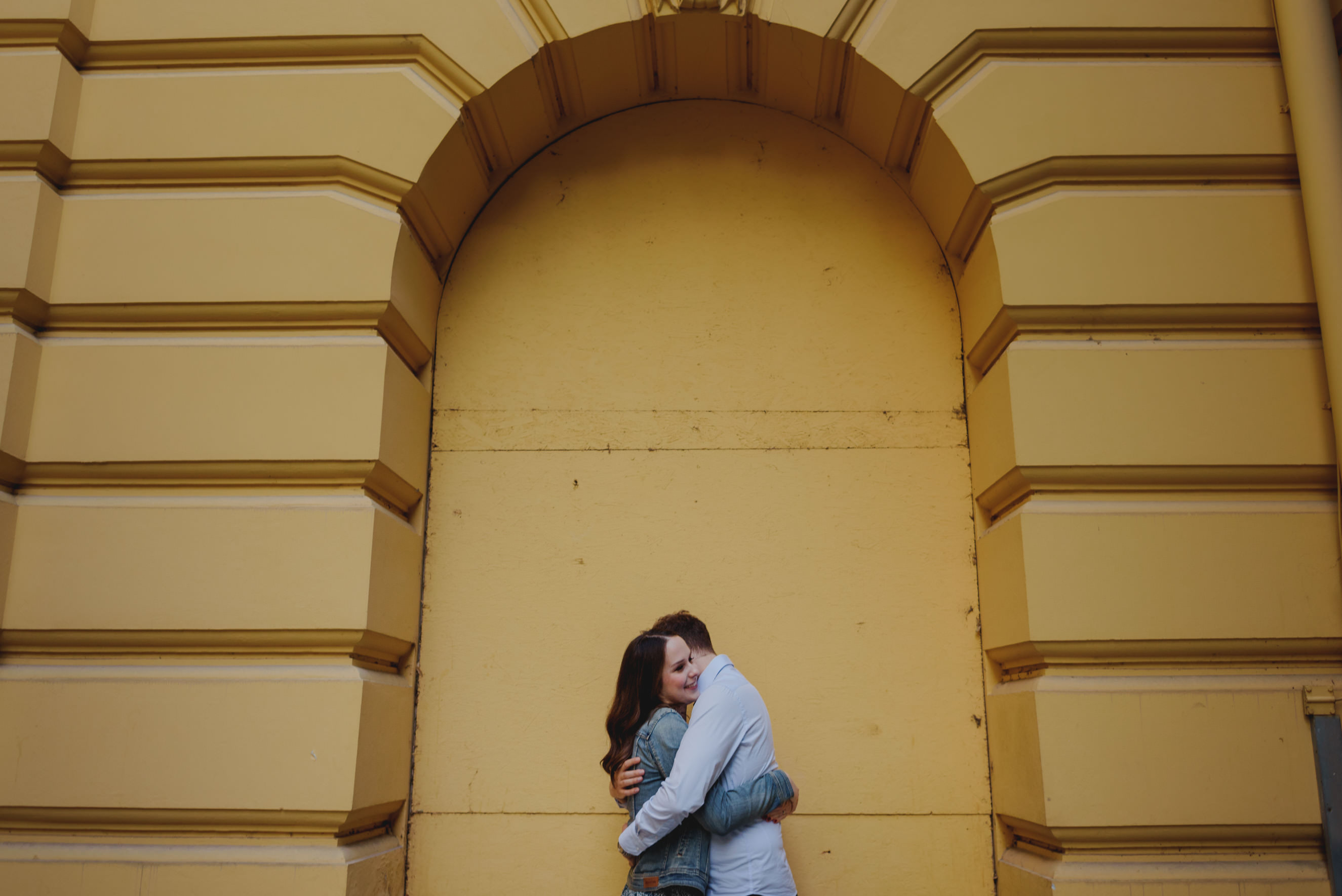 couple hugging in front of a yellow wall on Tomislavac in Zagreb