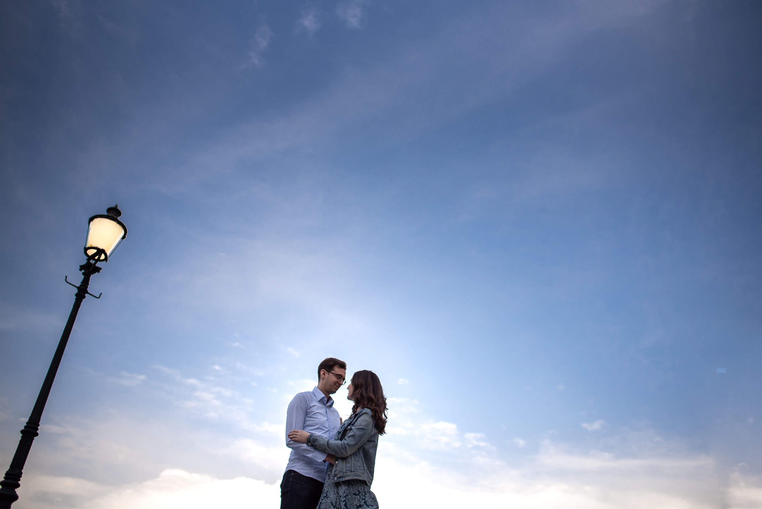 couple hugging under the skies with a lit light pole