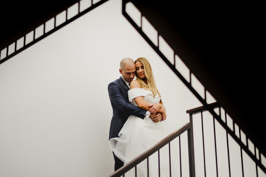 bride and groom hugging on a staircase