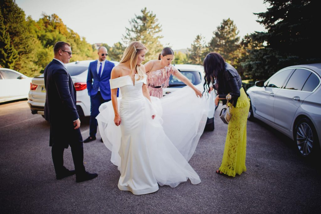 maid of honour fixing brides dress