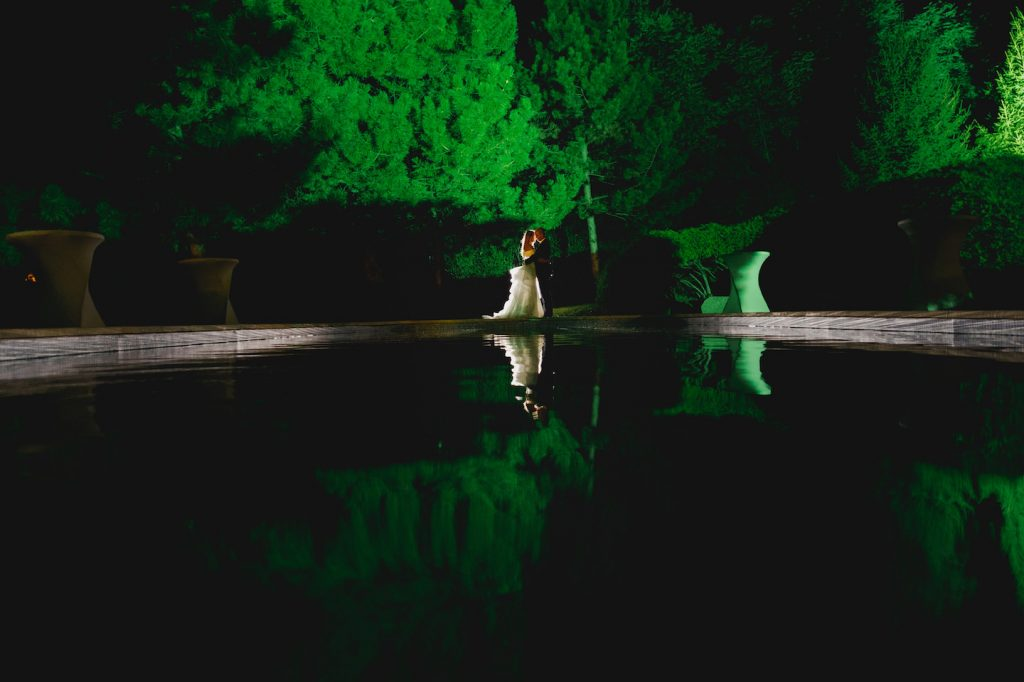 bride and groom hugging on the edge of the pool being backlit