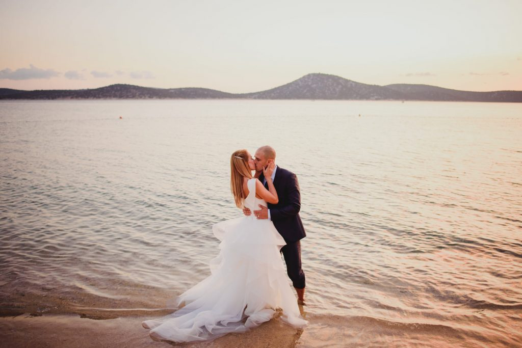 bride and groom kissing ankle deep in water