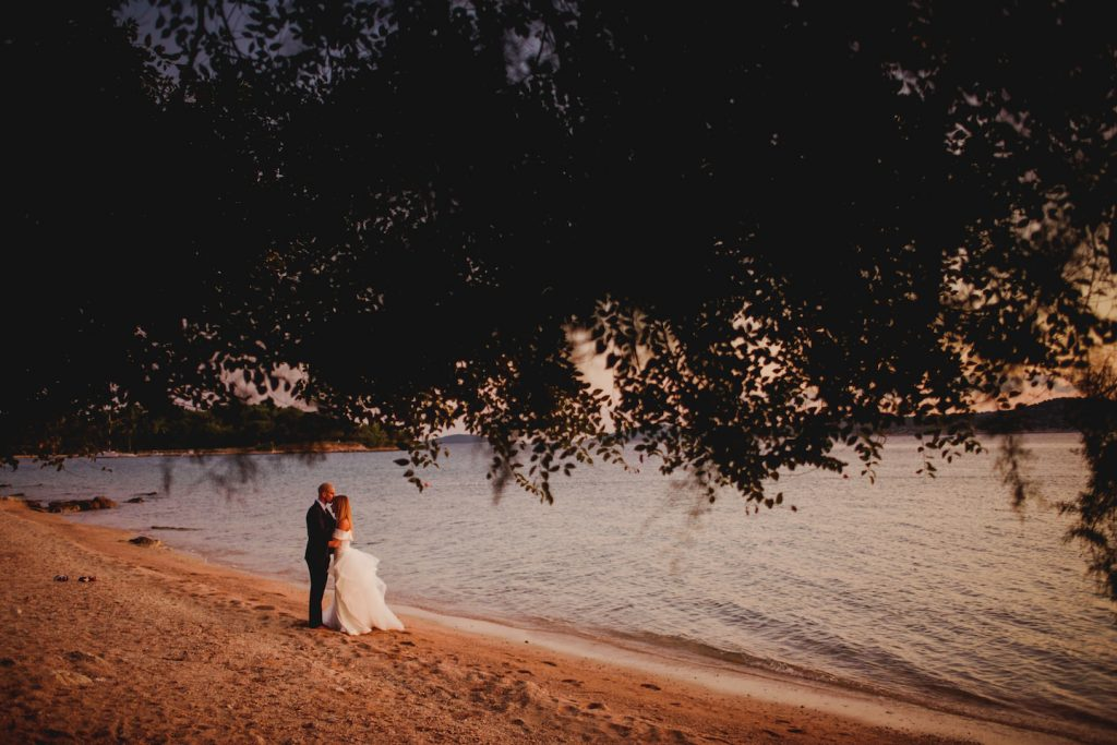 bride and groom hugging on a beach