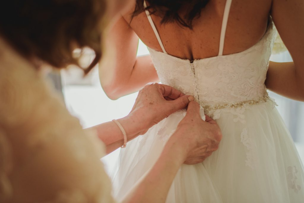 mother of bride helping bride to button up