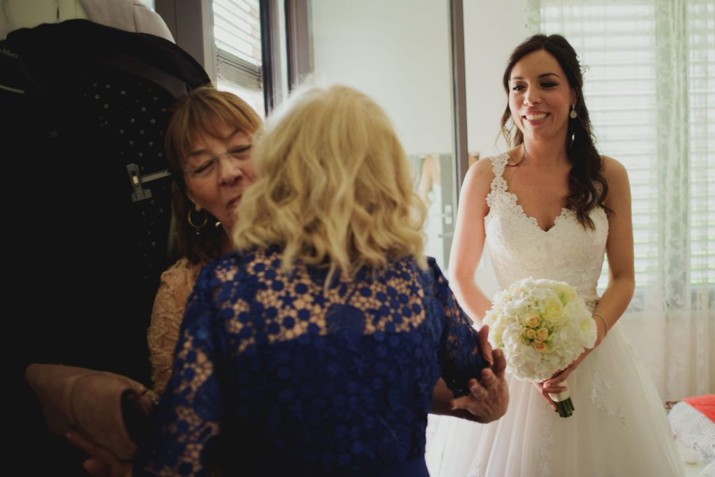 mothers of newlyweds hugging while bride is looking and smiling