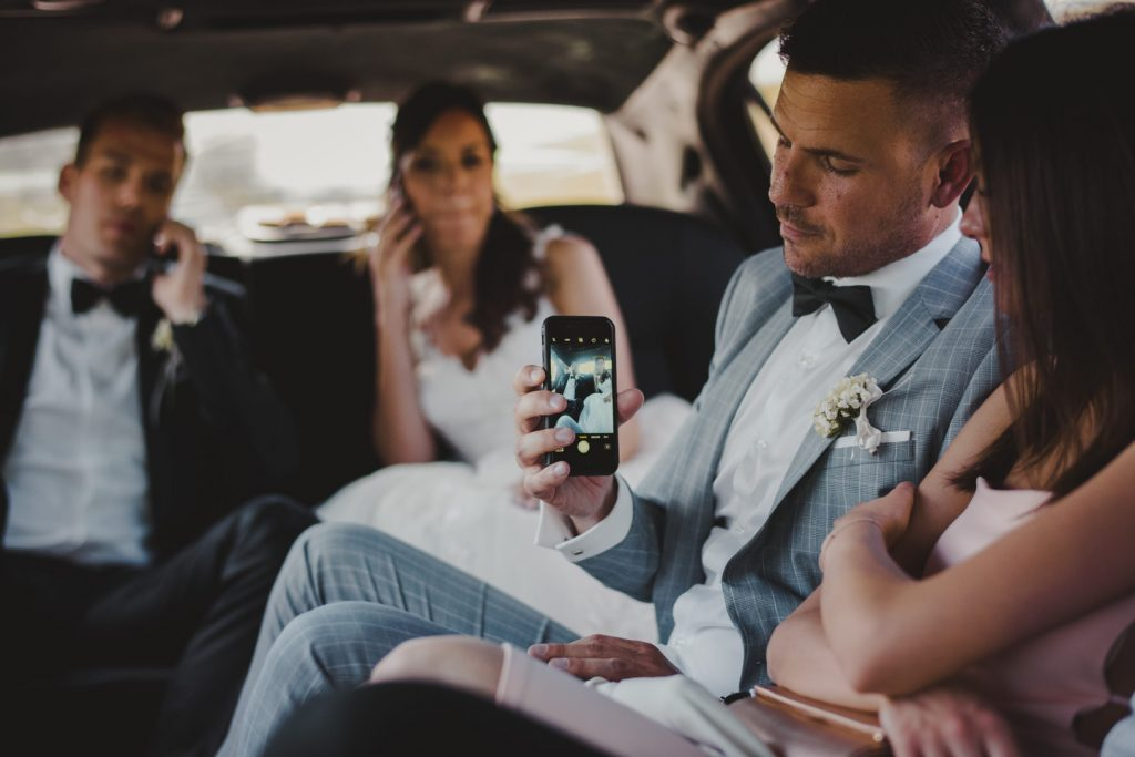 best man taking a photo of bride and groom in a limo