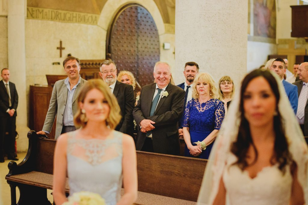 parents of groom looking at newlyweds during ceremony
