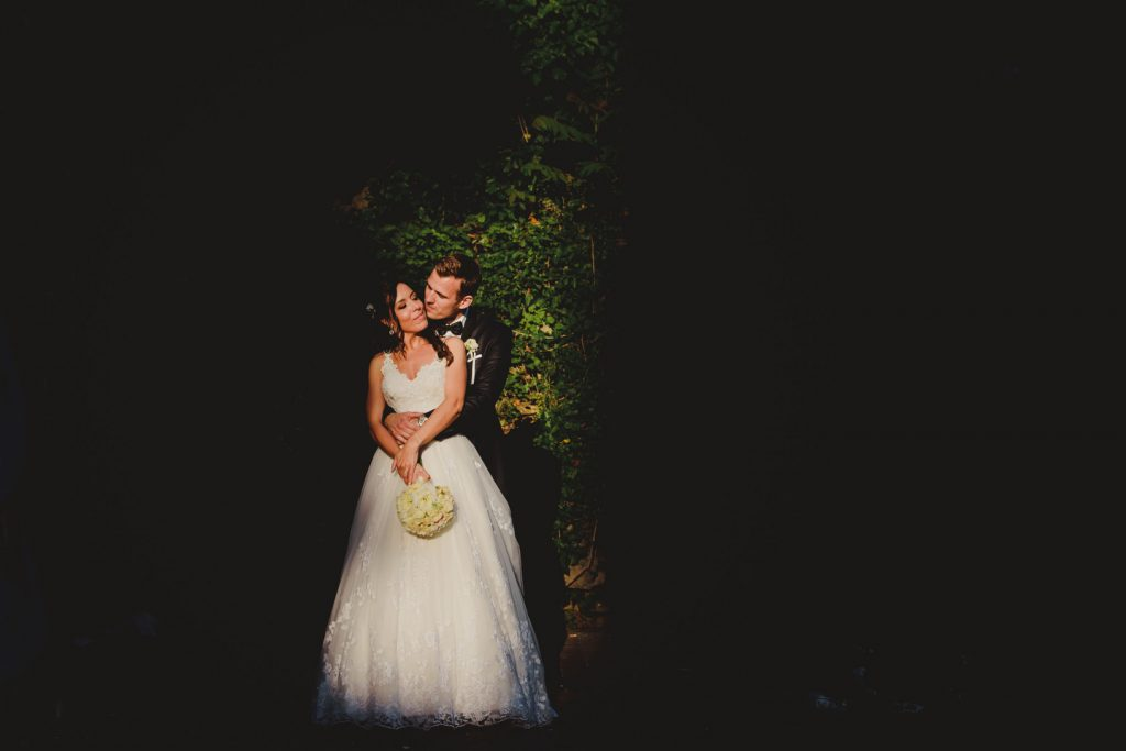 bride and groom kissing in a small patch of light