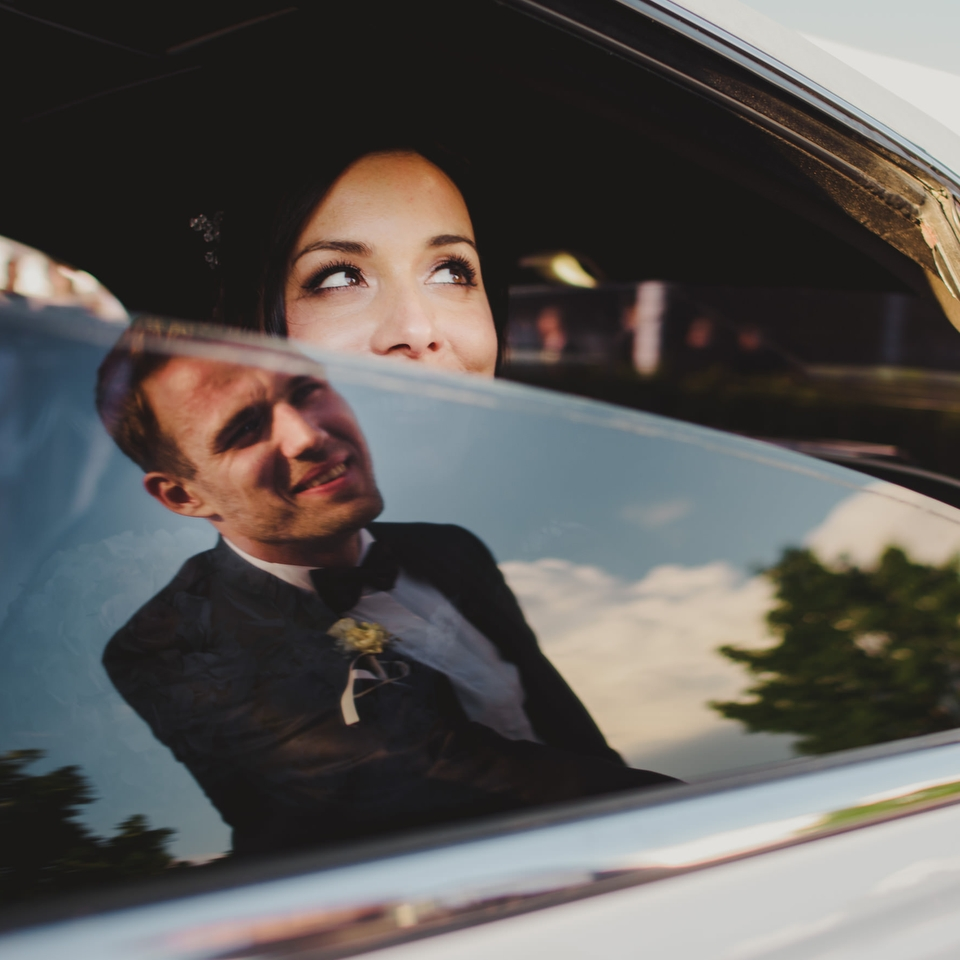 bride looking at groom from inside the car. groom seen in reflection of a glass. Riverside Golf