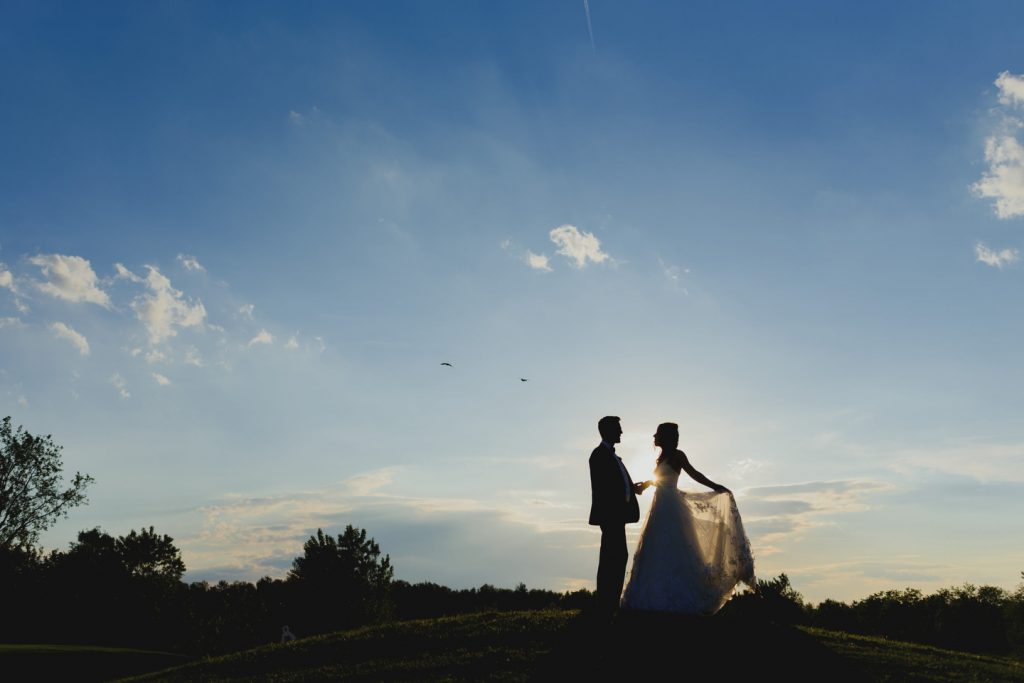 bride and groom dancing on a small hill