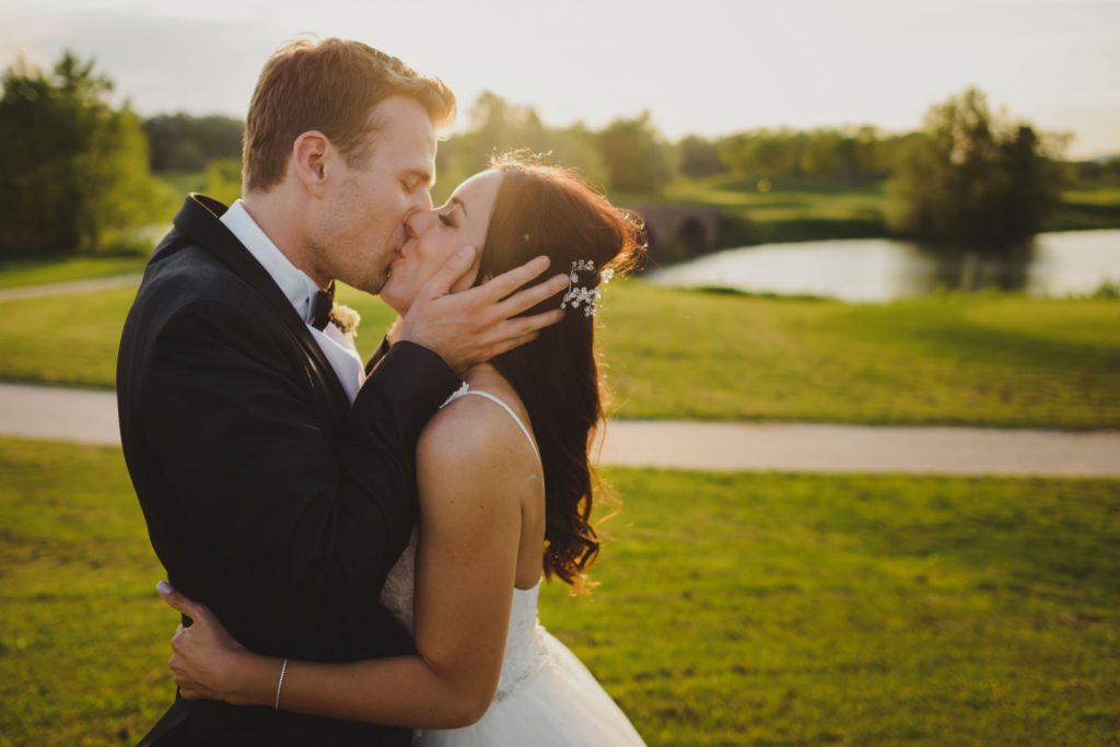 bride and groom kissing in the sunset