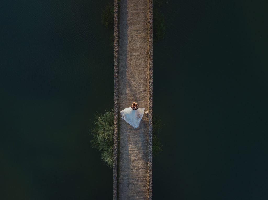 bride and groom dancing on a bridge shot on drone