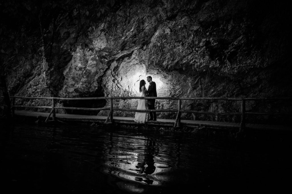 bride and groom hugging in front of the flash and huge rock