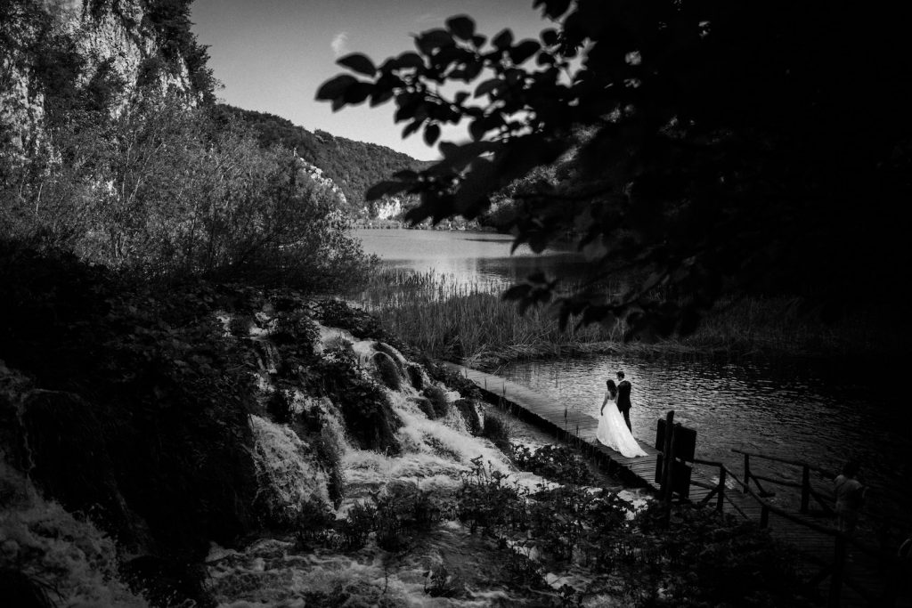 bride and groom walking over wooden bridge in plitvice lakes
