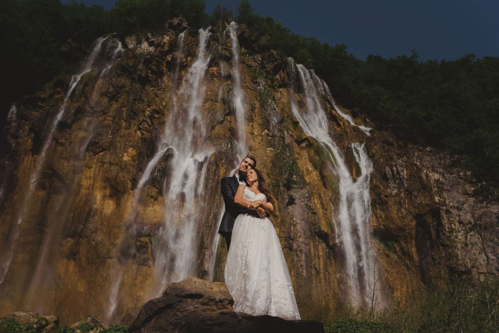 bride and groom hugging in front of the big waterfall on Plitvice Lakes