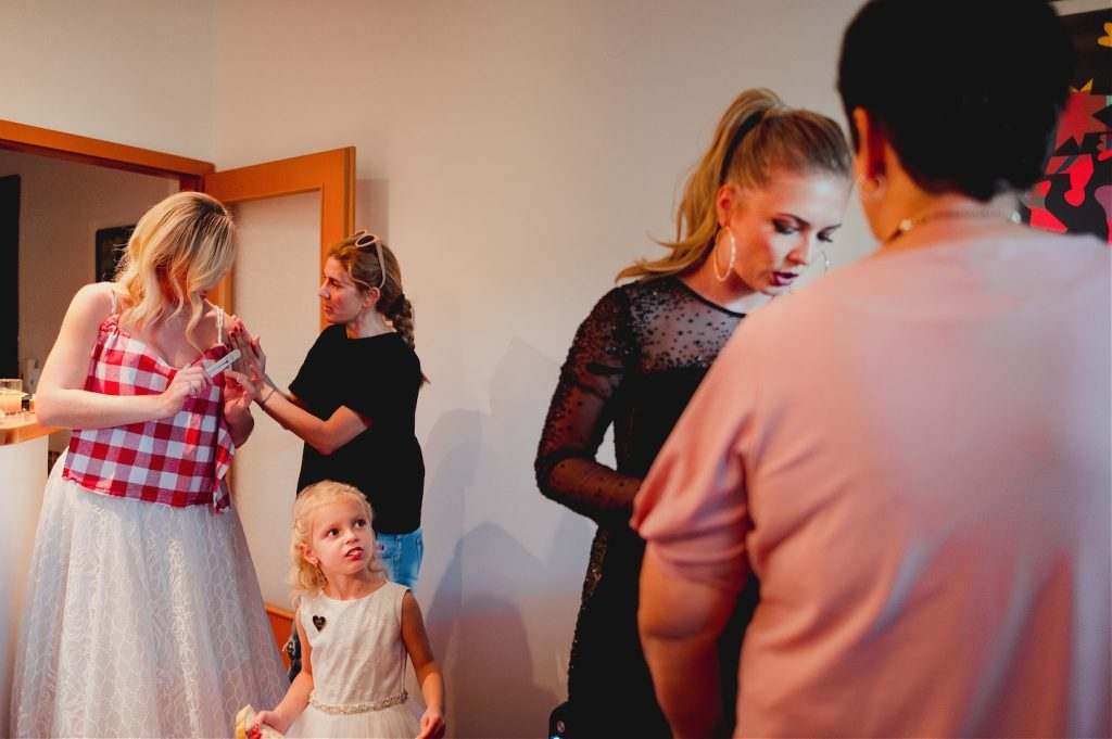 makeup artist fixing nails of the bride while her sister, mother and niece are all talking