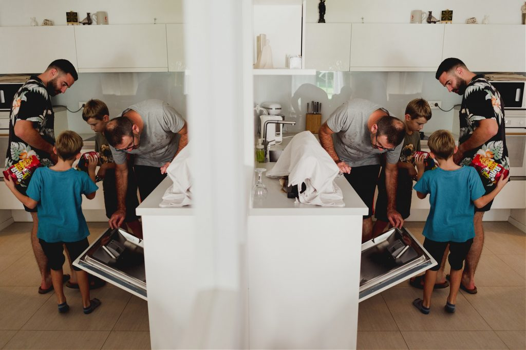 grooms father and his kids putting dishes in the washer