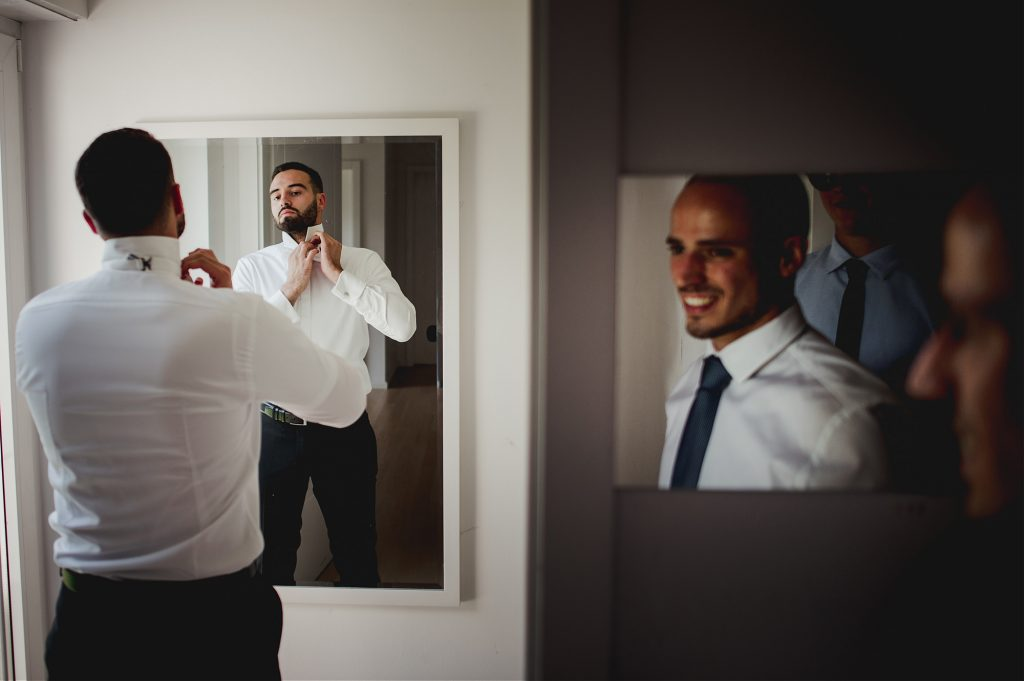 best man looking in the mirror groom getting ready