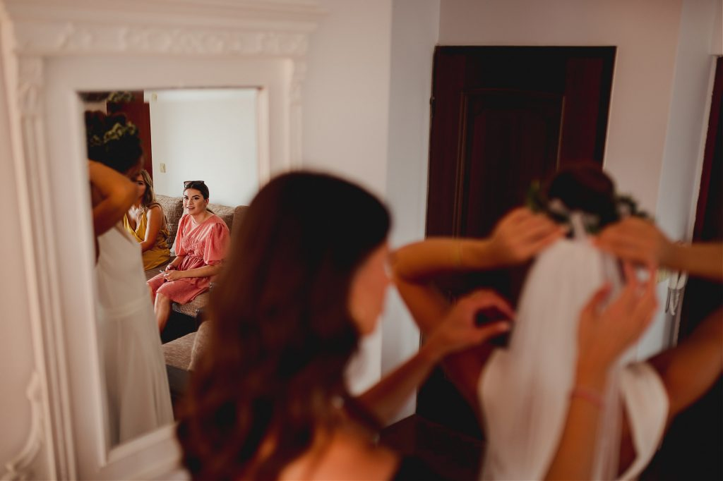 brides friends looking at her getting ready in the mirror