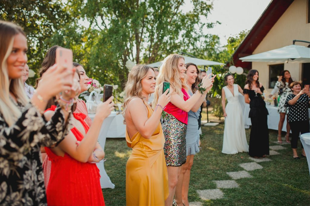 brides friends looking at the groom approaching the brides backyard with their cellphones recording