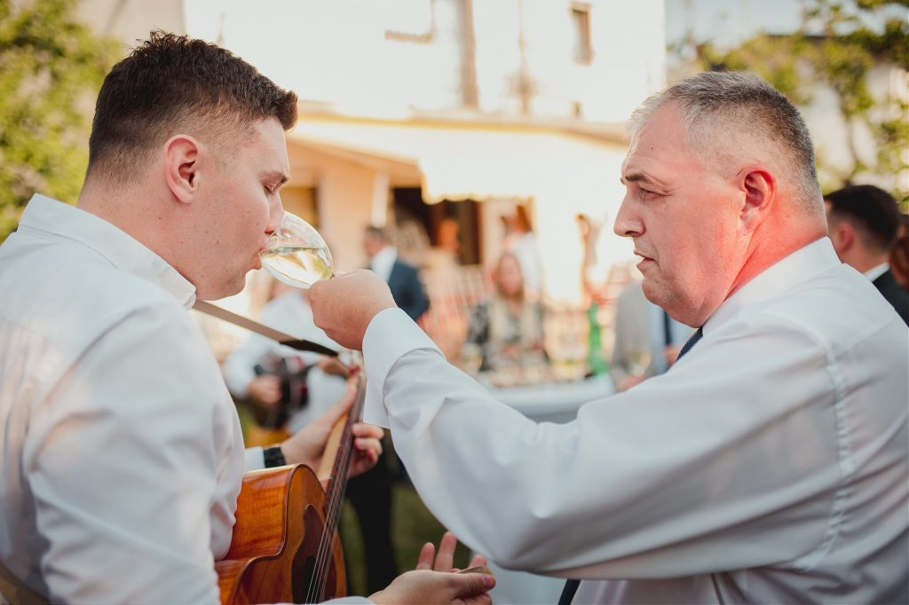 brides father gives wine to guitar player