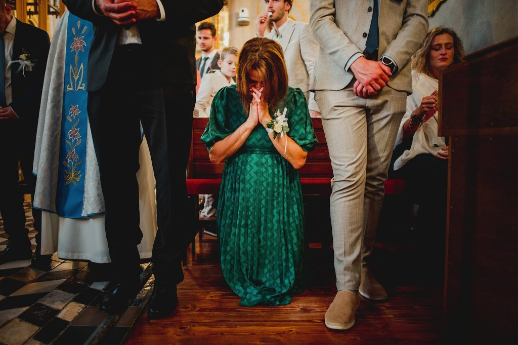 grooms mother praying during ceremony in church in Remete, Zagreb