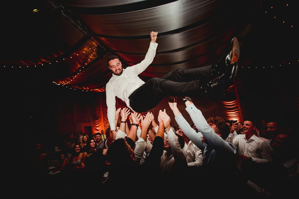 wild party throwing groom in the air in Kornati wedding and events